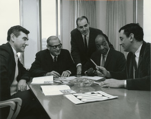 Five male members of business administration sitting and standing around a table