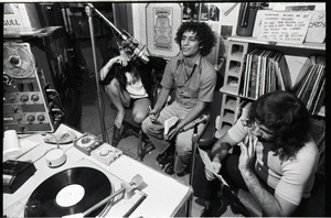 Abbie Hoffman: Hoffman (center) seated at microphone, WBCN studio, holding copy of Steal This Book