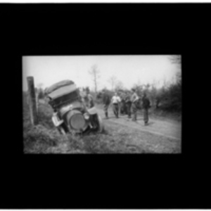 Car in a ditch, surrounded by bystanders