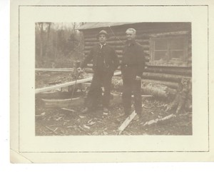 Log Cabin and two men Cellar Rats Building Cabin in Maine