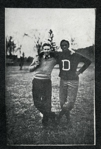 Unidentified student standing arm in arm with football coach Mathew W. Bullock