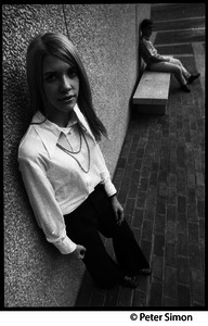 Stylishly Dressed Young Woman Leaning Against A Wall