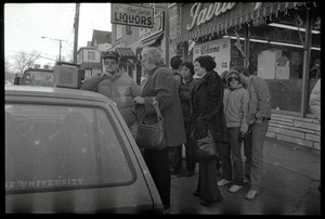 Crowd gathered about a radio perched on the hood of a car in Highland Falls, N.Y., listening to news of the arrival of the hostages from Iran