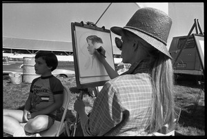 Artist drawing a sketch of a young boy at the Blandford Fair