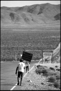 Activist on the road near the entrance to the Nevada Test Site holding a sign reading 'Stop nuclear weapons testing': Nevada Test Site peace encampment
