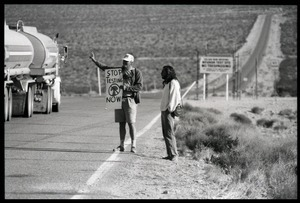 Activists flashing a peace sign at a passing truck by the road near entrance to the Nevada Test Site, holding a sign reading 'Stop testing now': Nevada Test Site peace encampment