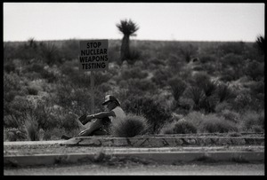 Activist seated by the road with a sign reading 'Stop nuclear weapons testing,' at the Nevada Test Site peace encampment