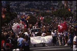 AIDS Emergency Fund marching in the San Francisco Pride Parade with float large in the rear: 'Every Penny Counts'