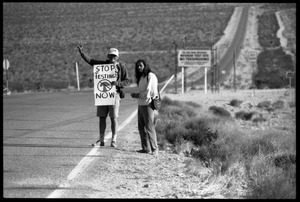 Activists standing by the road near entrance to the Nevada Test Site holding a sign reading 'Stop testing now,' at the Nevada Test Site peace encampment