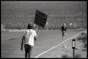 Activist on the road near the entrance to the Nevada Test Site holding a sign reading 'Stop nuclear weapons testing', wearing a t-shirt reading 'Nukes Het!': Nevada Test Site peace encampment