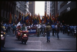 Marchers in the San Francisco Pride Parade with pride flags and banner 'Proud / Strong United 1987'