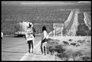 Activists on the road near the entrance to the Nevada Test Site, holding a sign reading 'Stop testing now': Nevada Test Site peace encampment