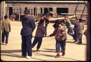 Children in circle game -- male teacher