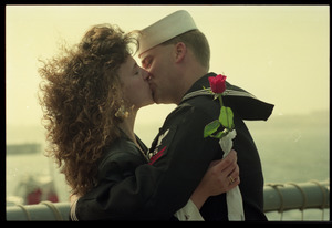 Woman with a rose kissing a sailor from the USS Roberts returning from Persian Gulf War duty