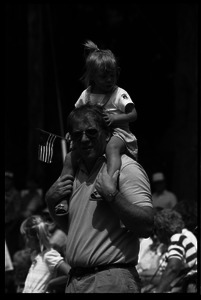 Girl waving a small American flag, sitting on her father's shoulders watching the Chesterfield's Fourth of July parade