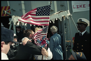 Sailor hugging a woman behind flags upon the USS Roberts returning from Persian Gulf War duty