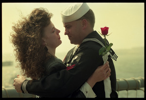 Woman with a rose embracing a sailor from the USS Roberts returning from Persian Gulf War duty