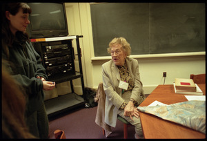 Julia Child, seated at a table, talking with students