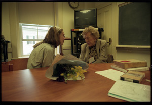 Julia Child, seated at a table, talking with a student
