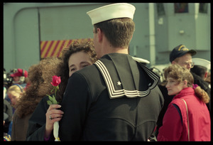 Woman with a rose hugging a sailor from the USS Roberts returning from Persian Gulf War duty