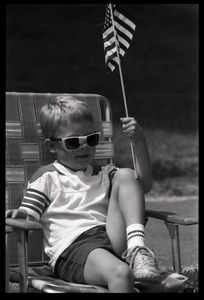 Boy with sunglasses in a lawn chair, waving an American flag and watching the Chesterfield's Fourth of July parade