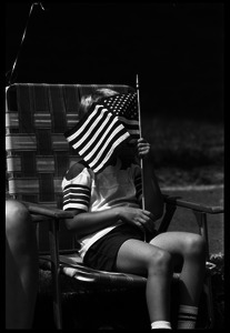 Boy in a lawn chair, ducking behind a small American flag while watching the Chesterfield's Fourth of July parade