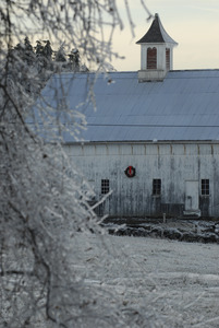 Barn hung with a Christmas wreath and ice-covered landscape