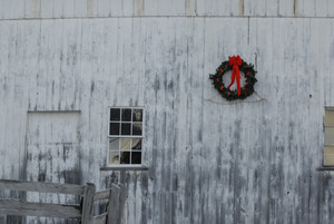 Christmas wreath hung on the side of a barn