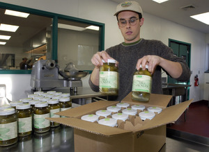 Young man packing jars of Real Pickles pickles for shipment