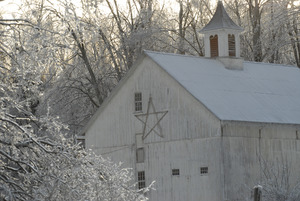 Barn with center cupola and Christmas star amid ice-covered trees