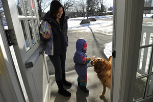 Mother and child leaving the New Salem Public Library, greeted by a waiting golden retriever