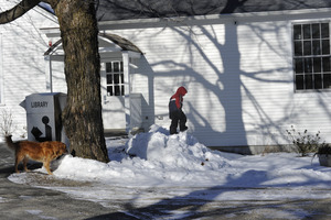 Child and golden retriever playing in snow in front of new New Salem Public Library