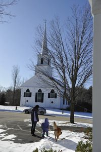 Mother, child, and golden retriever in the show in front of the New Salem Public Library, with 1794 Meeting House (First Congregational Church) in background