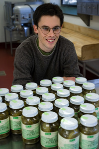 Young man seated in front of jars of Real Pickles pickles