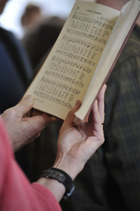 Aftermath of the Congregational Church fire in West Cummington, Mass.: close-up of parishioner singing from a hymnal