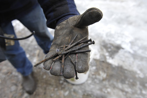 Aftermath of the Congregational Church fire in West Cummington, Mass.: man holding charred nails from the original church
