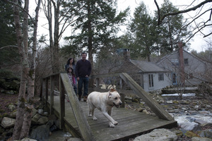 Sheffield House: Martin Canellakis, Faith Cromas, and daughter Eva, and Poppy, their yellow Labrador retriever, walking across a wooden bridge, Sheffield, Mass.