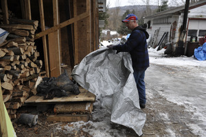 Aftermath of the Congregational Church fire in West Cummington, Mass.: man pulling a tarp away from the charred remains of the church bell