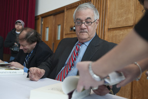 Author Stuart Weisman and Congressman Barney Frank (l. to r.) seated at a table in the Student Union Ballroom stage, UMass Amherst, signing copies of his biography