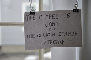 Aftermath of the Congregational Church fire in West Cummington, Mass.: sign on the wall 'The chapelis gone but the church stands strong'