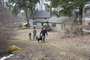 Sheffield House: Martin Canellakis, Faith Cromas, and daughter Eva, and black Labrador retriever walking by their house, Sheffield, Mass.