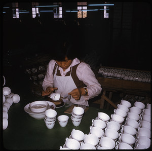 Ceramics factory: woman applying transfer design to tea cups