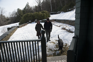 Couple and their dog walking through the snow toward the porch at Naulakha, Rudyard Kipling's home from 1893-1896