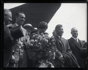 Amelia Earhart reception: Earhart with bouquet of flowers, flanked (l. to r.) by Louis Gordon (co-pilot and mechanic) and Wilmer Stultz (pilot), Gov. Alvan T. Fuller at far right