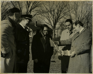 Randolph W. Bromery, Allen Torrey, Fire Chief Doherty, Mike Sullivan, and Jack Littlefield, standing outdoors reading a paper