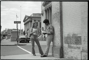 Free Spirit Press crew member sharing copy of the magazine with young African American man on street corner near Springfield City Hall