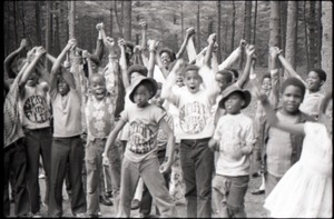 Inner City Round Table of Youth campers: group of African American children at summer camp, some wearing Spirit in Flesh t-shirts, raising hands and cheering