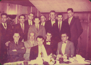 Faculty members gathered behind a dining table