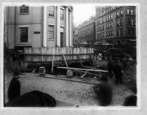 Construction at the corner of Park St., showing wood fence in front of a hole, with pedestrian and trolley traffic in the background
