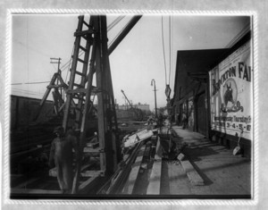 Construction site, including workers and a crane, in front of a billboard for Brockton Farm